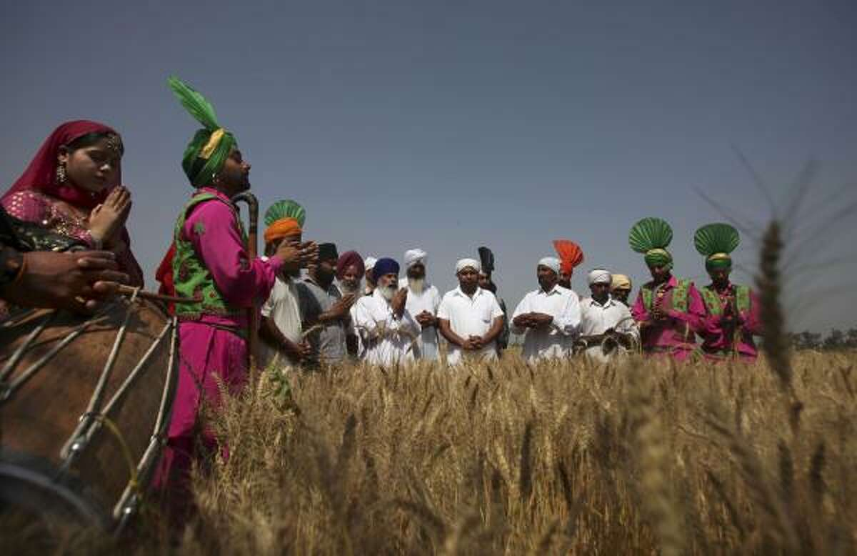 Folk artists in their traditional attire and villagers do a prayer to thank for a good crop, as part of Baisakhi celebrations in Ajnala, some 35 kilometers (22 miles) from Amritsar, India, Monday, April 12, 2010. Baisakhi, a harvest festival celebrated in the Punjab region, also marks the beginning of the Sikh New Year.