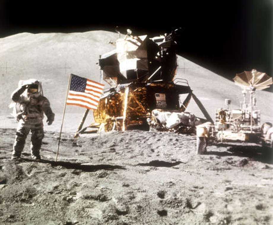 Astronaut James Irwin salutes a U.S. flag planted on the surface of the moon during the Apollo 15 mission.  The lunar module is at center with Hadley Delta in the background, and the lunar rover vehicle driven by the astronauts waits at right. Photo: AP File