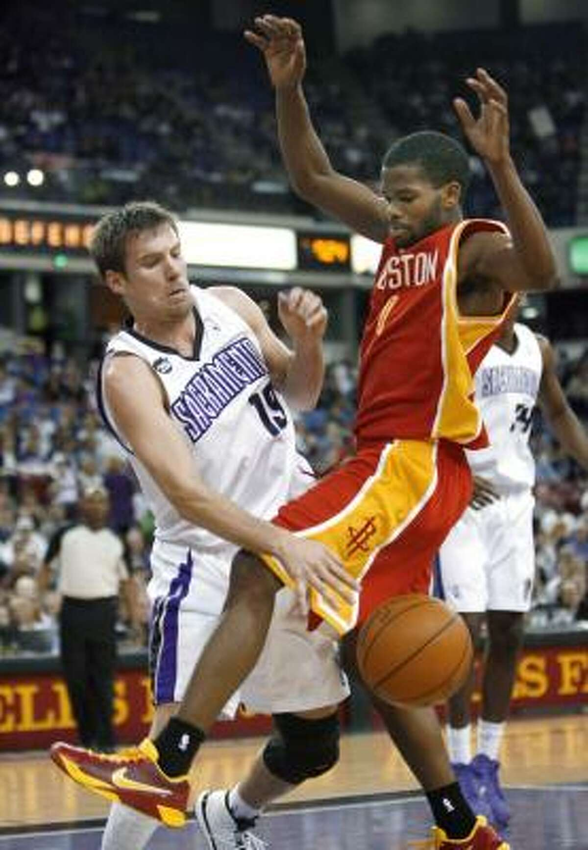 Rockets guard Aaron Brooks, right, has the ball batted away by Kings guard Beno Udrih, but Brooks was still one of five Rockets in double-figures.
