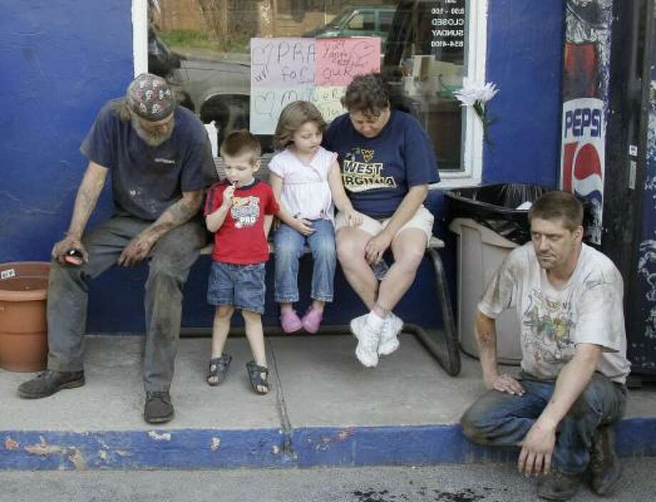 In Whitesville, W.Va., Jerry Bearfield, Jaden Clemons, 3, his sister Gabrielle Clemons, 4, their grandmother Gladys Clemons, and Jerry's brother, Randy Bearfield, take part in a moment of silence for the miners. Photo: Amy Sancetta, AP