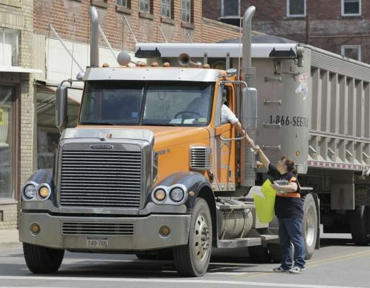 A truck driver stops to donate money to Miranda Clemons in downtown Whitesville, W.Va., on Monday, to raise money for the families of the miners.