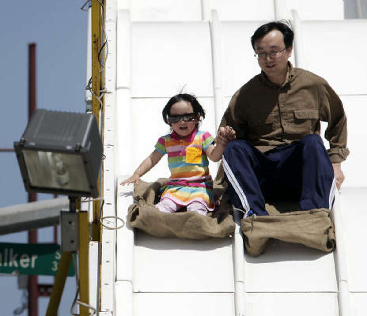 Xiaogang Han and his 2-year-old daughter, Missy, slide down a slide during the Houston Children's Festival in downtown Houston, Texas.