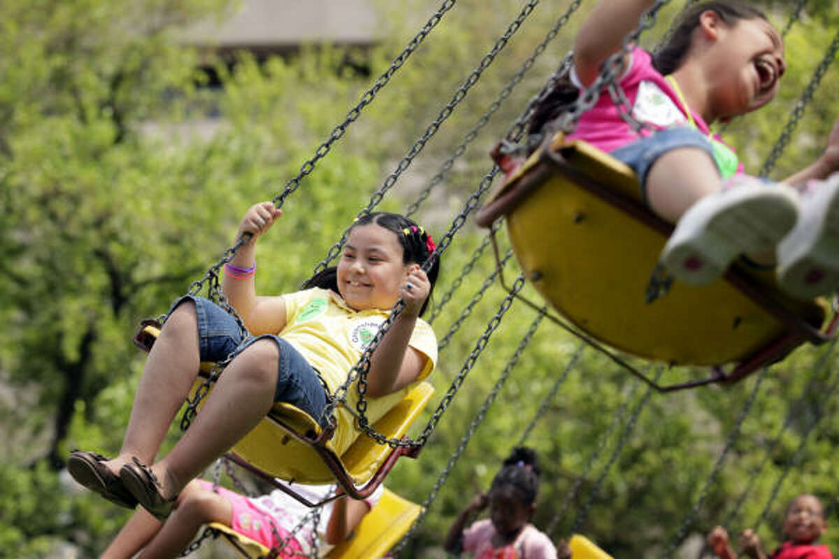 6-year-old Carla Perez, left, rides the swings with her 6-year-old cousin, Jasmine Aguilar, right, during the Houston Children's Festival, in downtown Houston, Texas.