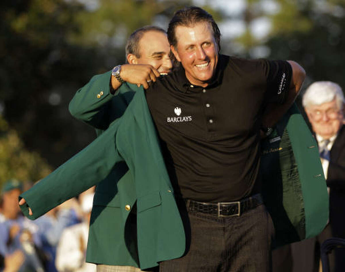 Angel Cabrera, left, the 2009 Masters champion helps Phil Mickelson put on his Masters jacket after his win at the 2010 Masters.