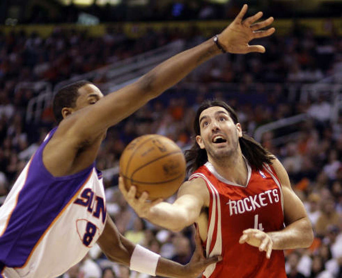 Rockets forward Luis Scola, right, attempts a layup under the out stretched arm of Phoenix Suns center Channing Frye.
