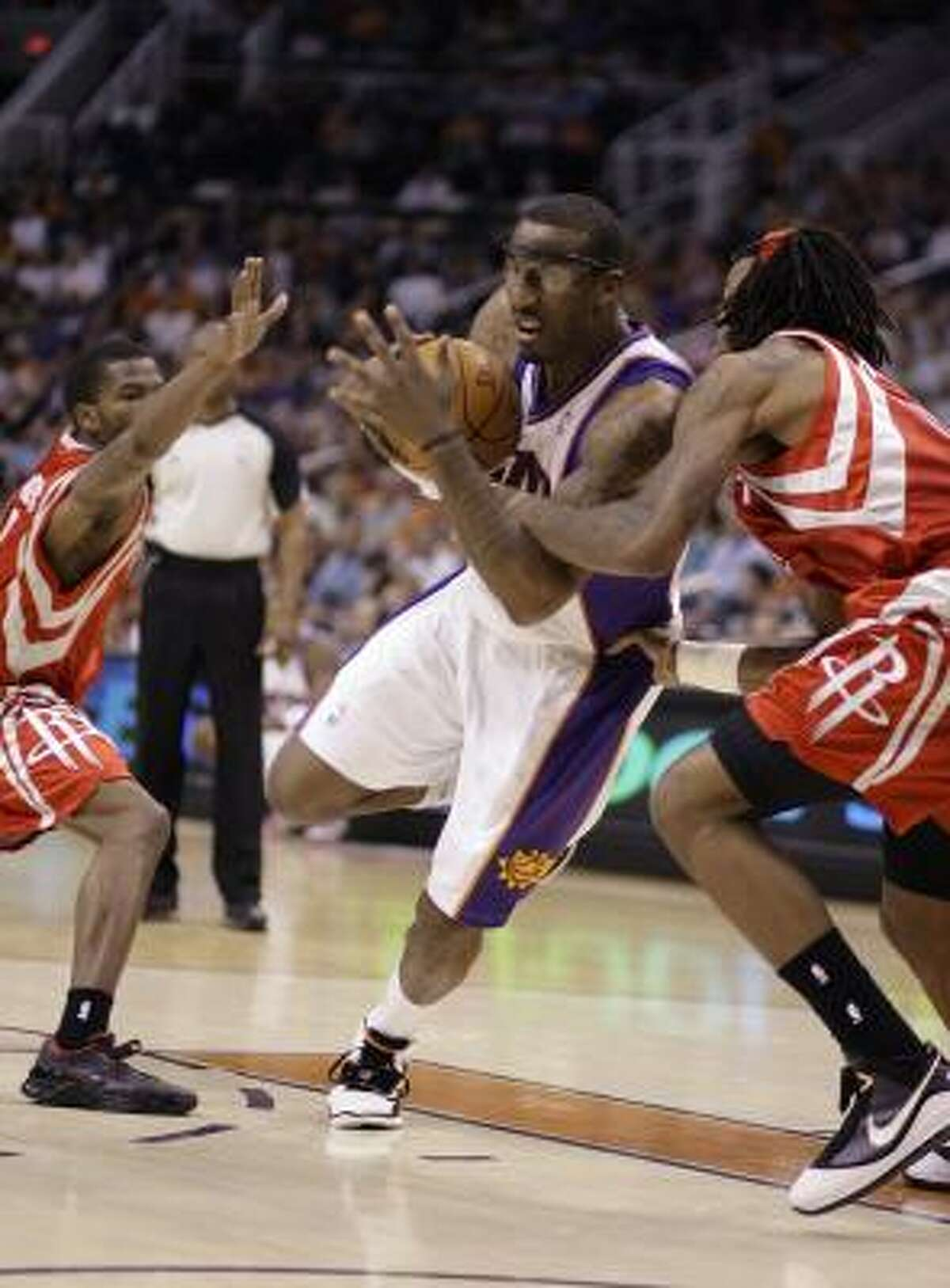 Phoenix Suns forward Amare Stoudemire, center, drives to the basket between Rockets guard Aaron Brooks, left, and forward Jordan Hill.