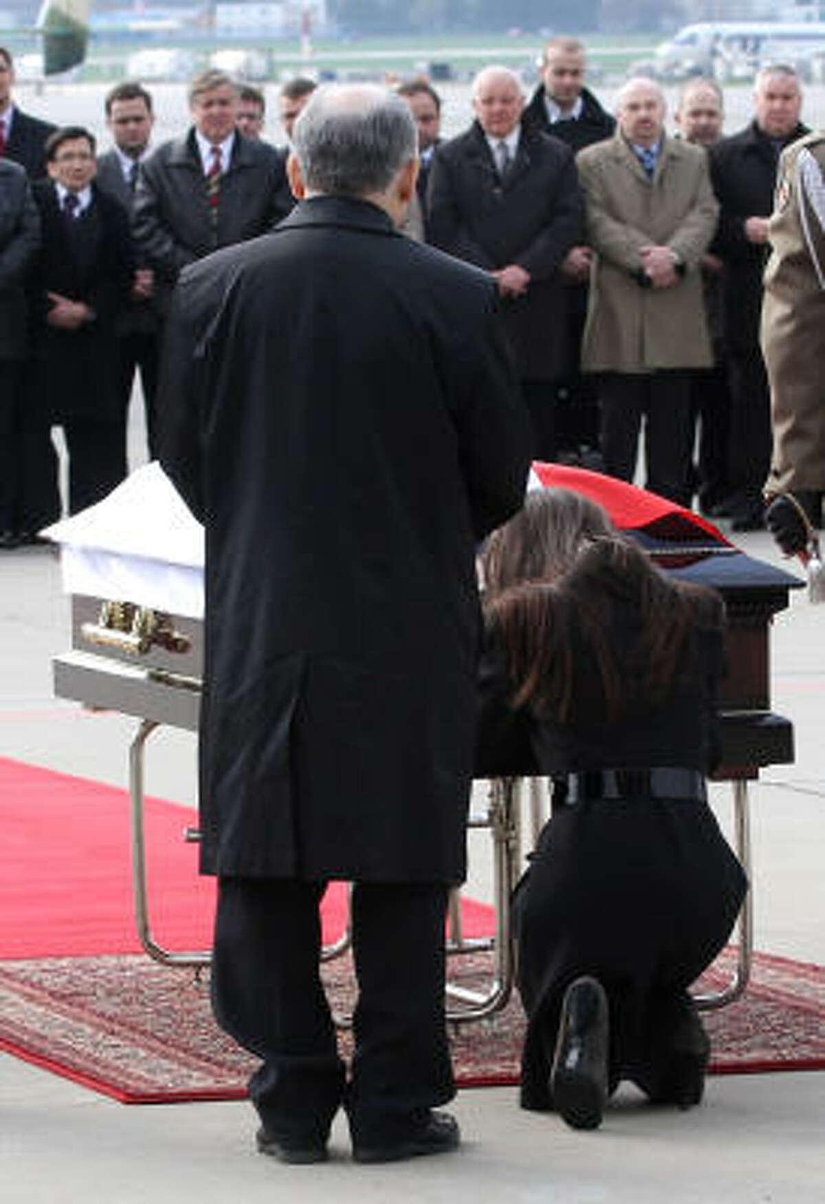 Jaroslaw Kaczynski, twin brother of late Polish President and daughter Marta Kaczynska pray by the coffin of president Lech Kaczynski after its arrival in Warsaw.
