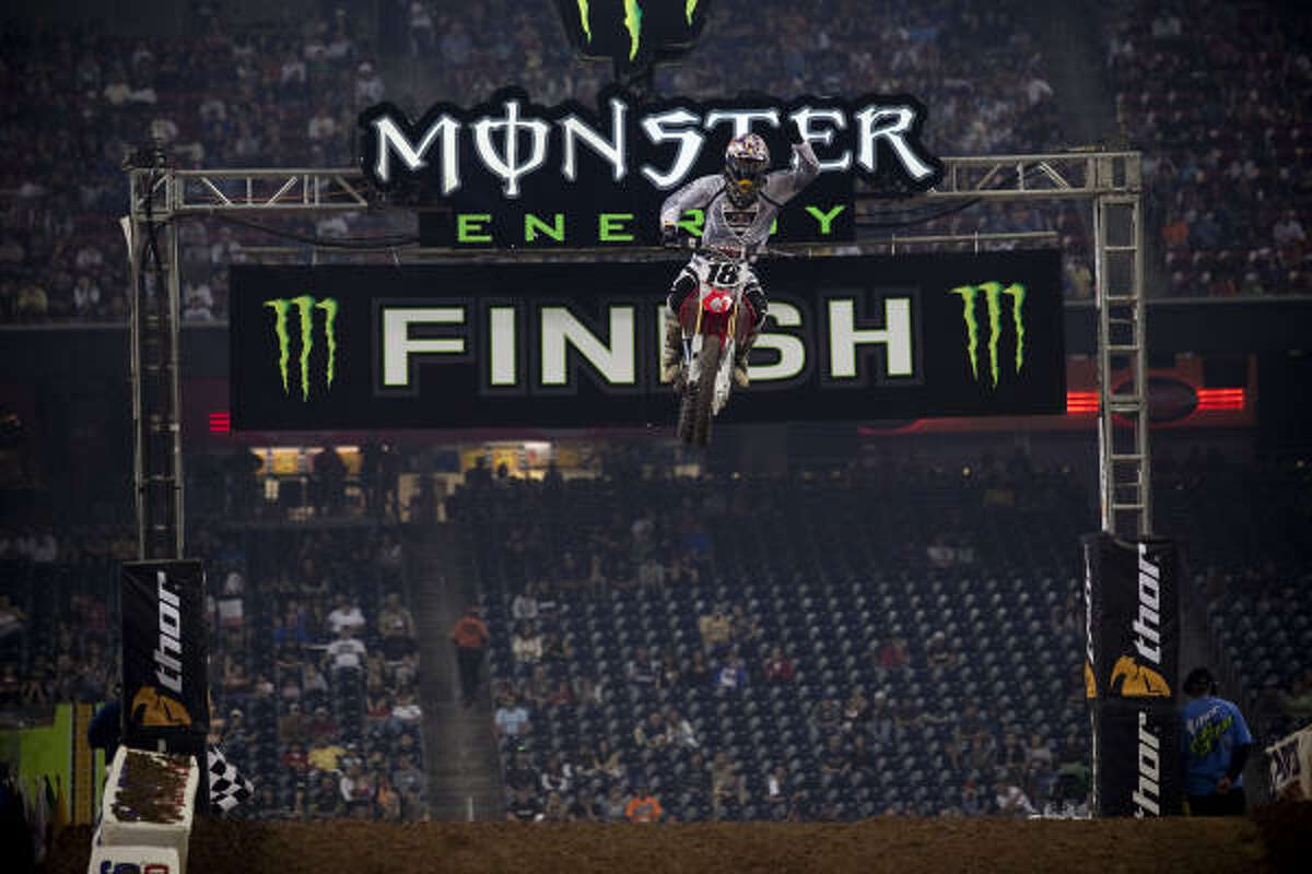 David Millsaps jumps over the finish line after winning his heat.