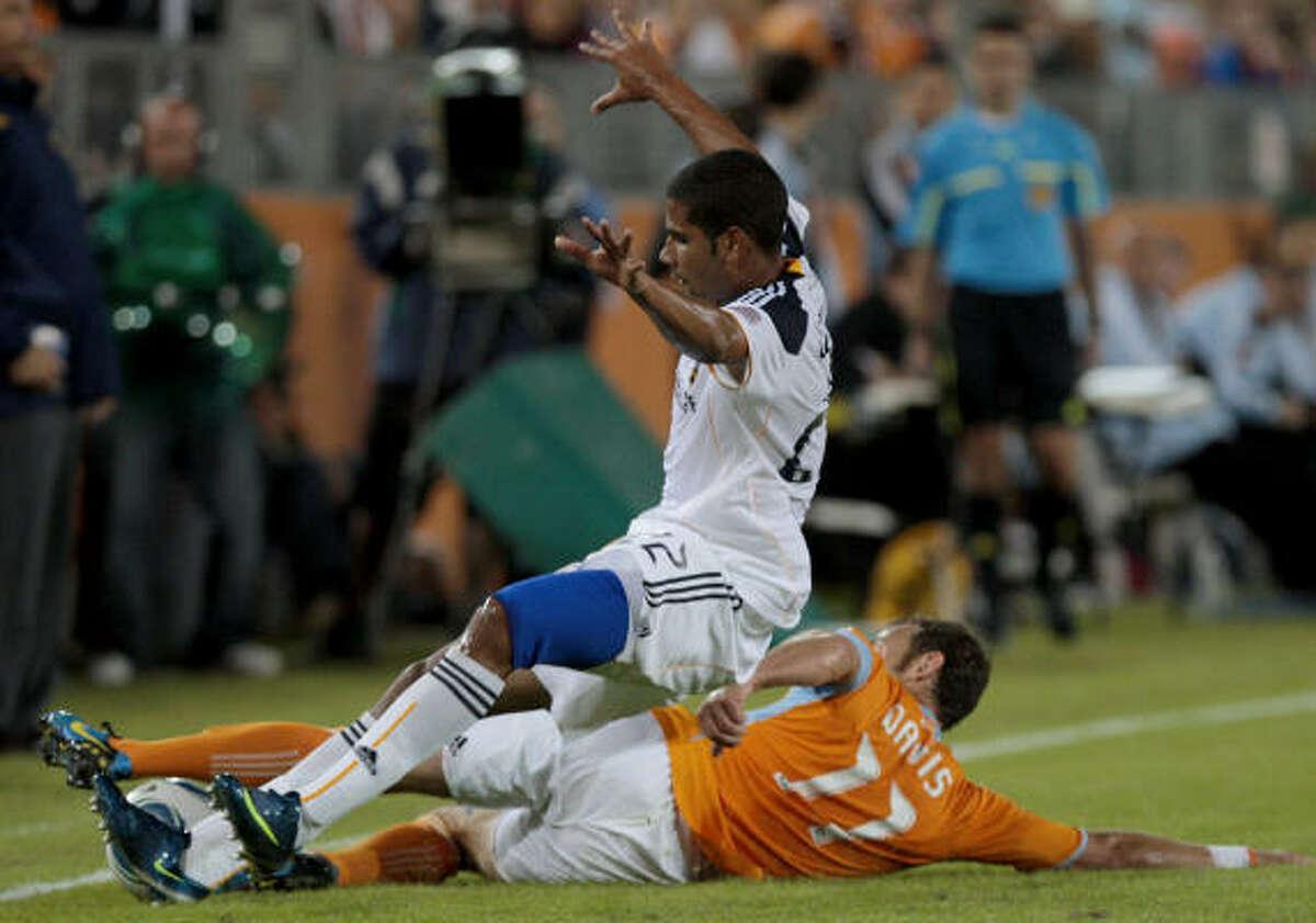Dynamo midfielder Brian Davis slide tackles Los Angeles' Leonardo during Saturday's match at Robertson Stadium. Los Angeles won 2-0.
