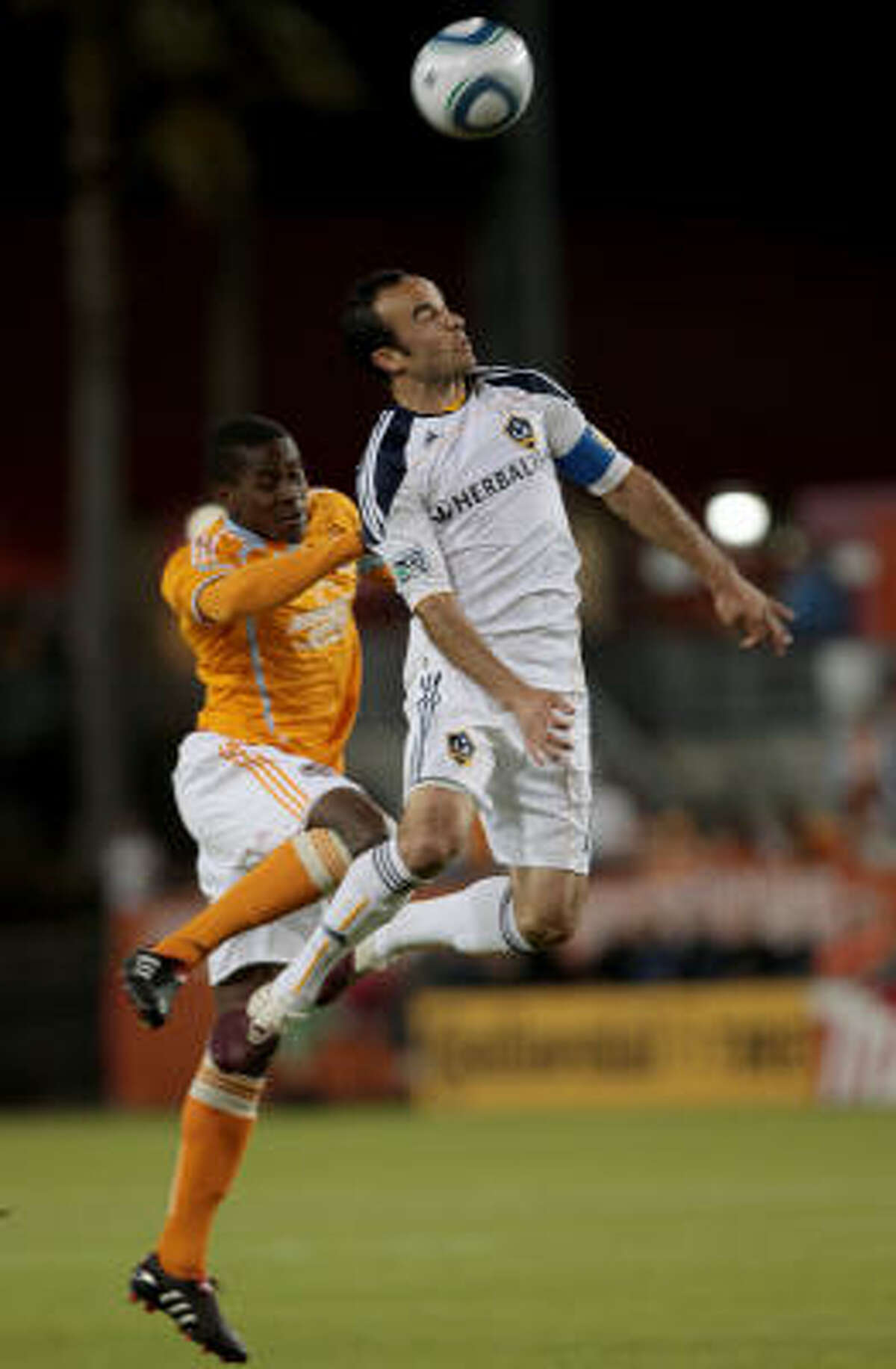 Houston's Lovel Palmer tries to defend Landon Donovan as he goes up for a header.