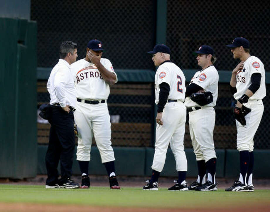 Manager Brad Mills and the outfielders check on left fielder Carlos Lee after he was hit by the ball during the third inning. Photo: Karen Warren, Chronicle