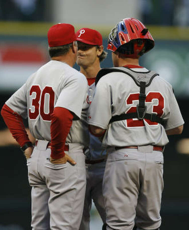 Phillies pitcher Jamie Moyer reacts as he is visited on the mound by pitching coach Rich Dubee and catcher Brian Schneider after Hunter Pence's homer. Photo: Karen Warren, Chronicle