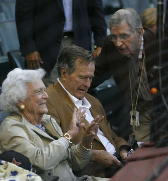 Former President George H.W. Bush and Barbara Bush settle into their seats during the first inning.