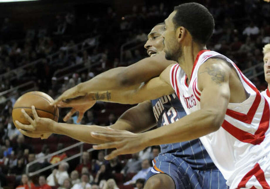 Charlotte's Boris Diaw, left, is fouled by Rockets forward Jared Jeffries during the first half of Friday's game at Toyota Center. The Rockets won 97-90. Photo: Pat Sullivan, AP