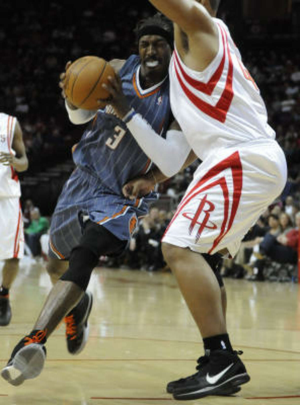 Charlotte's Gerald Wallace drives past Rockets center Chuck Hayes during the first half.