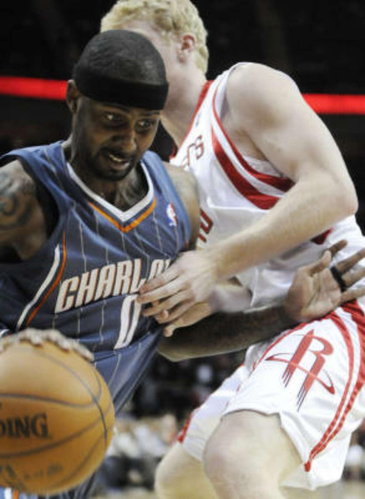 Bobcats guard Larry Hughes (0) pushes past Rockets forward Chase Budinger.