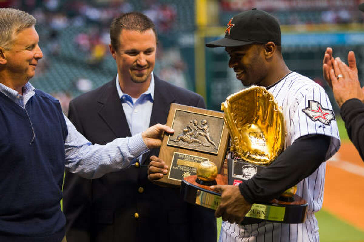 Astros center fielder Michael Bourn receives his 2009 Lou Brock Award as the National League stolen bases leader along with his 2009 Gold Glove Award, both presented by Astros general manager Ed Wade.