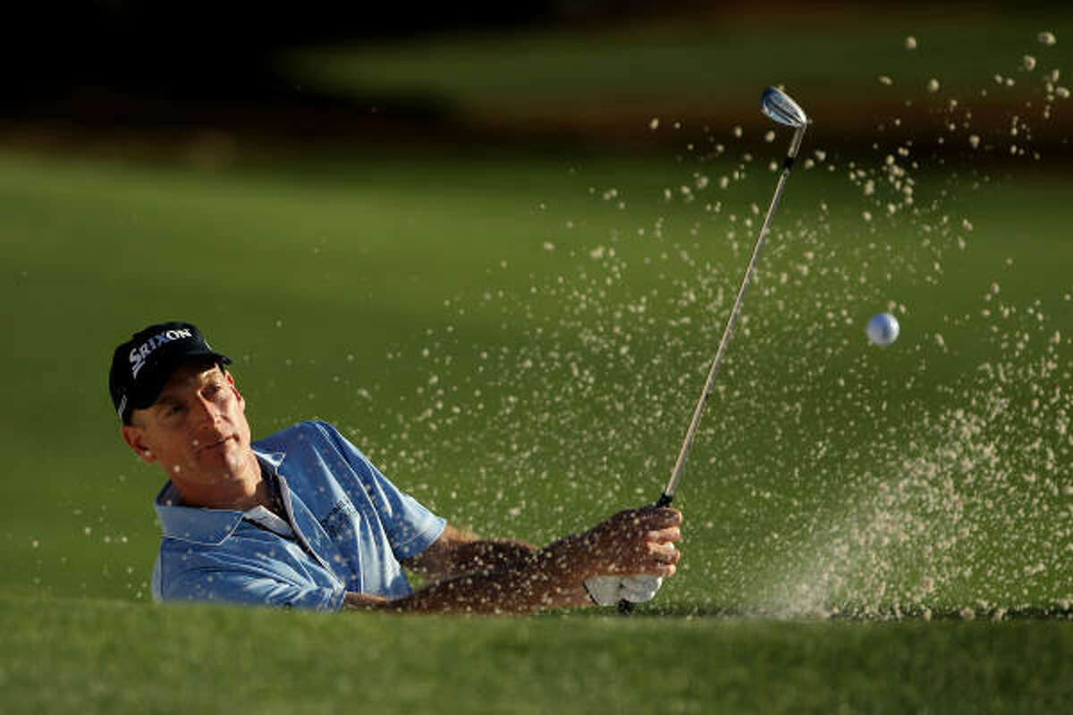 Jim Furyk plays from a bunker on the 18th hole.