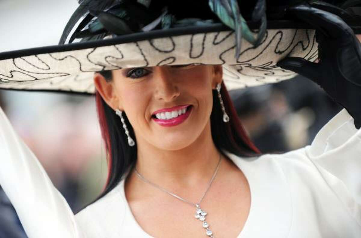 A racegoer poses for a photograph as she arrives for Ladies Day.
