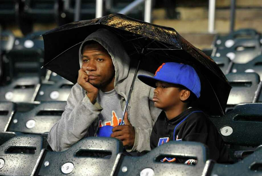 Jamal Long and his son Andre, of the Queens borough of New York, shield themselves from the rain with an umbrellas as they wait for a baseball game between the New York Mets and the Florida Marlins on Wednesday, Aug. 3, 2011, in New York. The game was postponed due to rain. (AP Photo/Kathy Kmonicek) Photo: Kathy Kmonicek