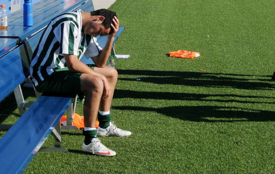 The Woodlands' Sebastian East sits dejected on the bench following the Highlanders 2-3 semifinal loss to Strake Jesuit. Photo: Patrick Meredith, For The Chronicle