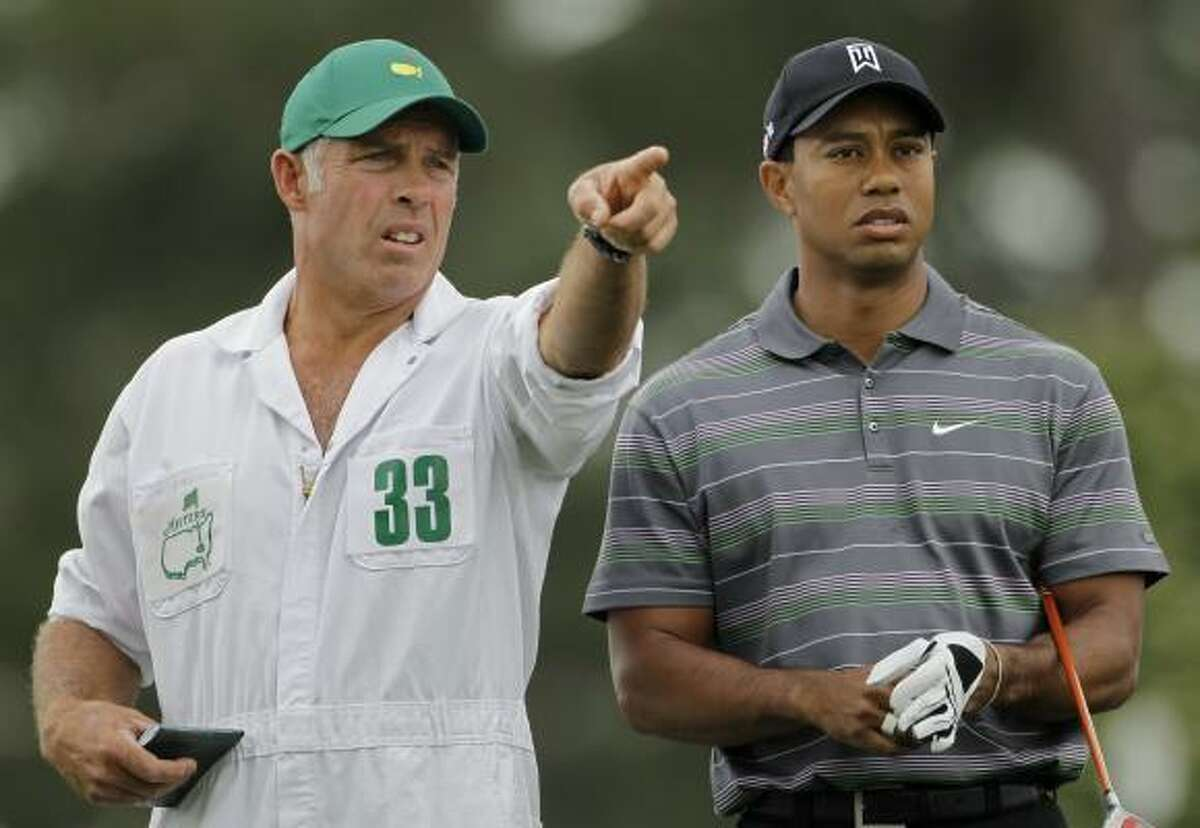 Tiger Woods gets instructions from caddie Steve Williams before teeing off at the first hole.