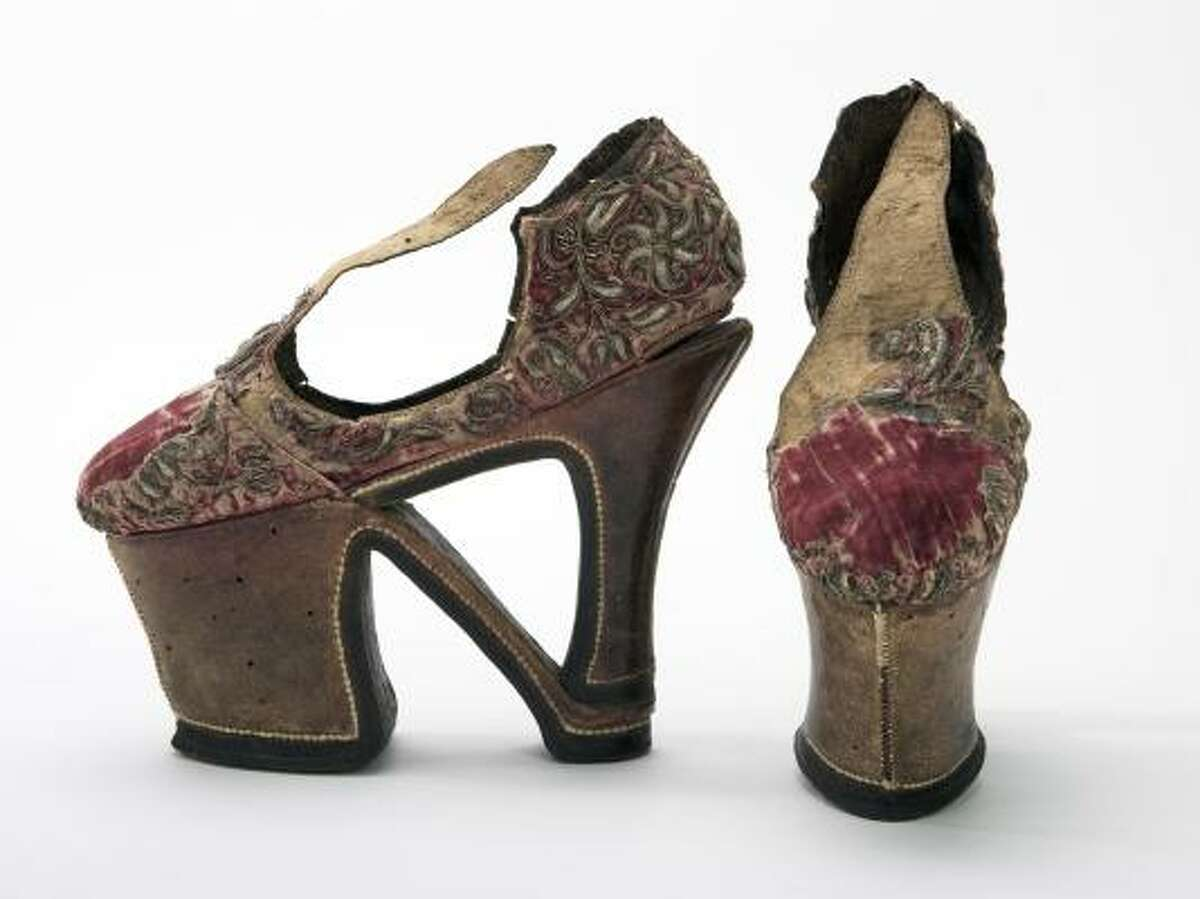 This red velvet upper is decorated with raised silver thread embroidery, and has an unusual sole. Talk about high heels. These shoes were dated back to the Renaissance in Europe. Read more on the history of shoes here.