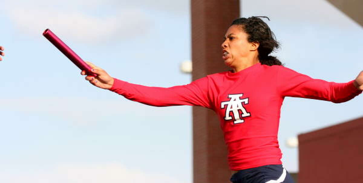 Alief Taylor's Whitney Grant hands off the baton in the 800-meter relay.