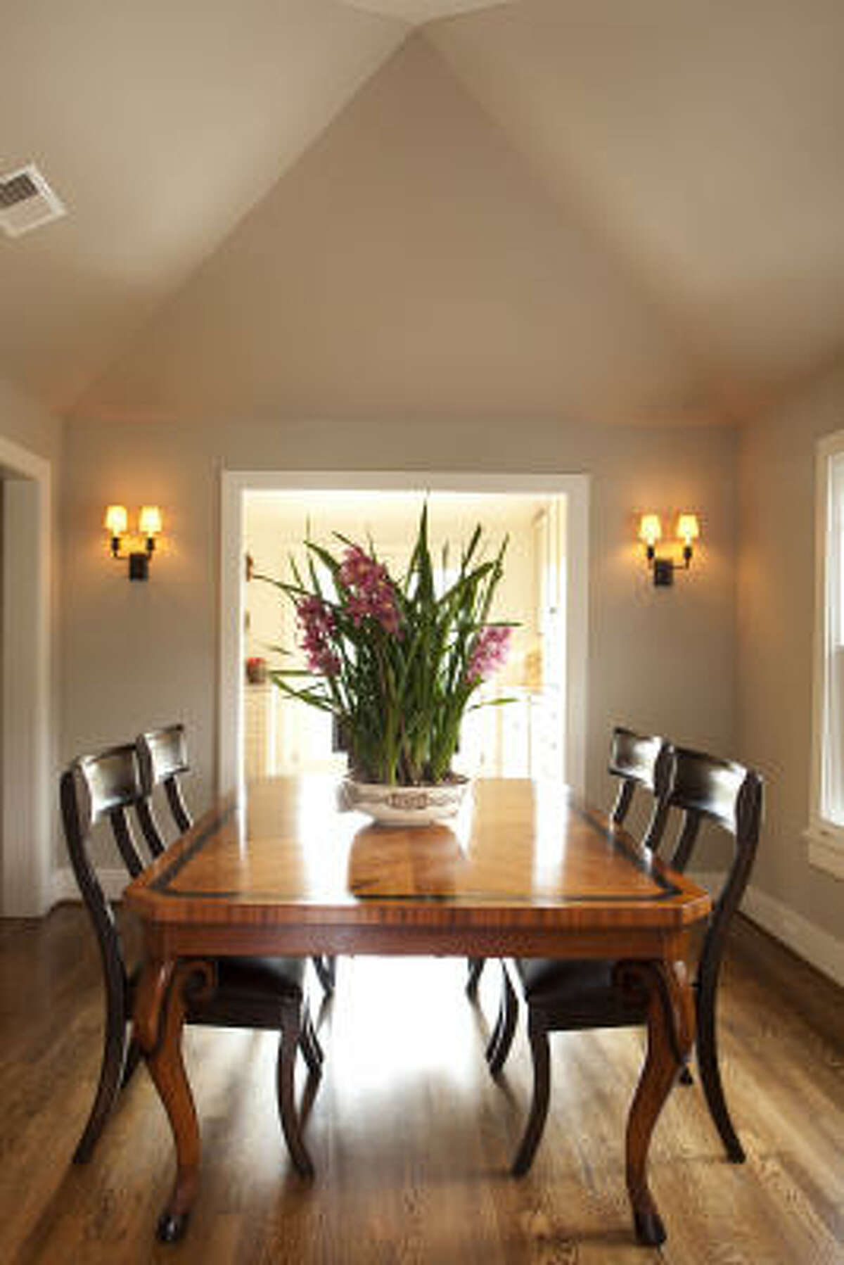 The dining room's vaulted ceiling makes the space feel larger than it is. The custom dining table features cloven hoof-style legs.