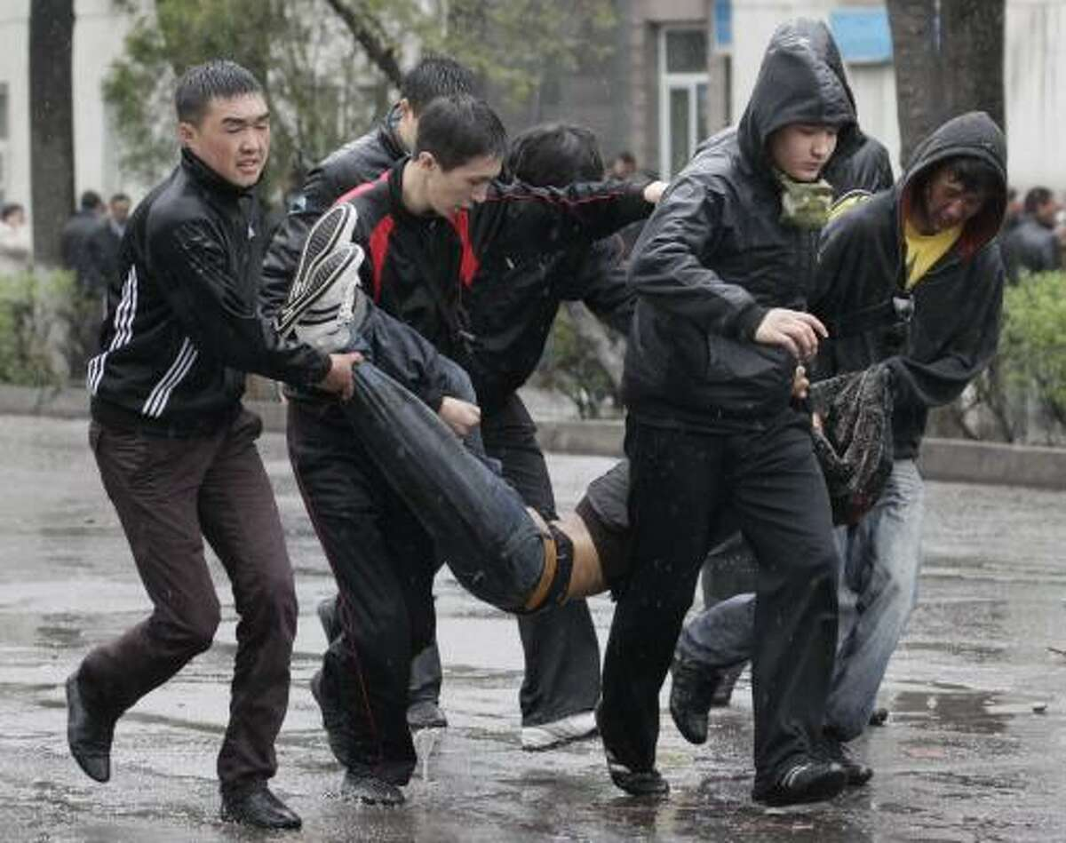 Kyrgyz protesters carry a wounded colleague during clashes with riot police in Bishkek, Kyrgyzstan.