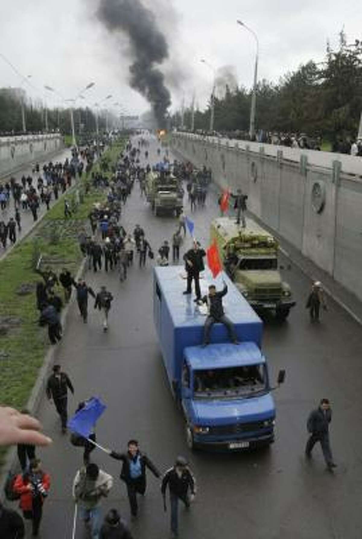 Kyrgyz protesters waving the national flag, ride on a truck in Bishkek, Kyrgyzstan.