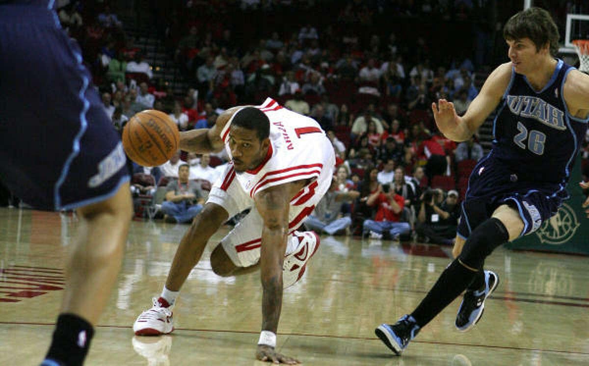 Rockets forward Trevor Ariza, left, dribbles to the basket with Jazz forward Kyle Korver defending.