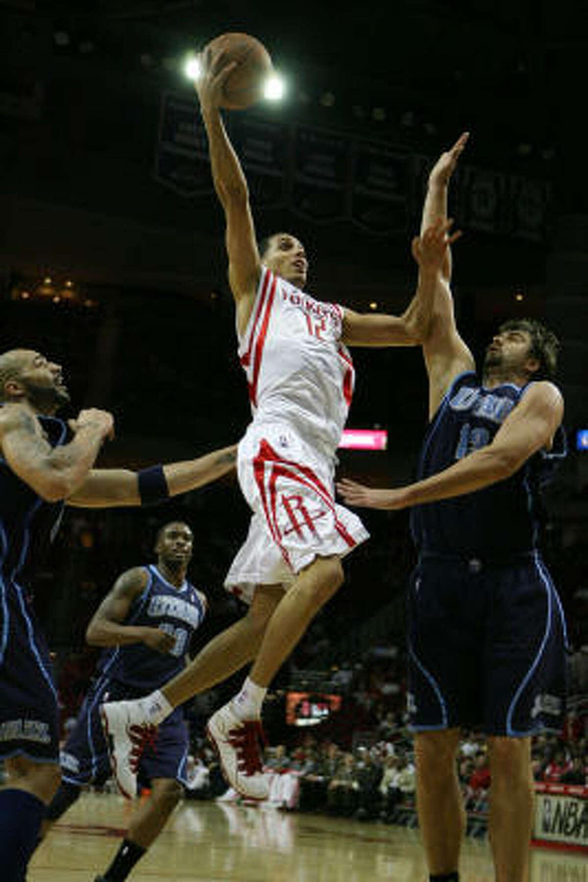 Rockets guard Kevin Martin, center, shoots over Jazz forward Carlos Boozer, left, and Jazz center Mehmet Okur.