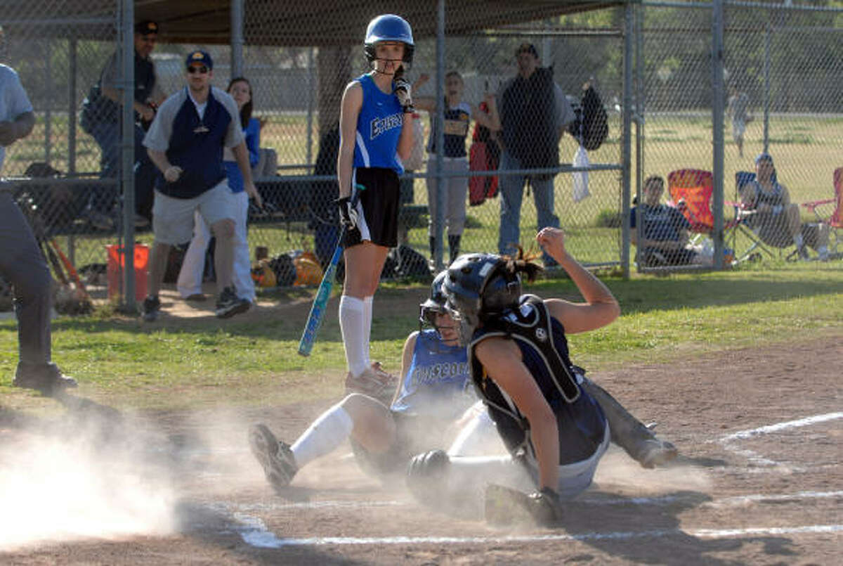 The dust flies as Episcopal's Mia Gerachis is called out at the plate.