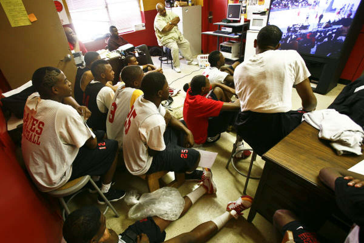 The Yates basketball team watches game film after a team practice at the Yates High School gym in Houston.