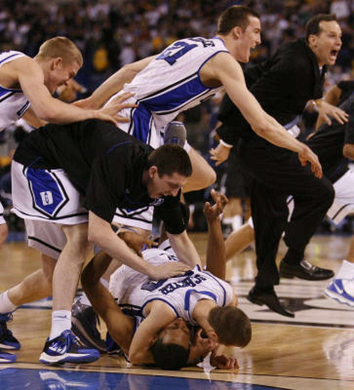 Duke guard Jon Scheyer (30) and Lance Thomas (42) celebrate their win as the dogpile starts after defeating Butler 61-59.