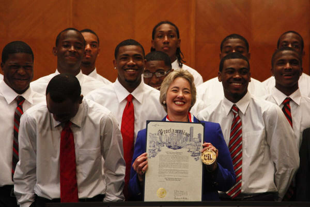 Houston City Mayor Annise Parker holds up a proclamation in honor of the Jack Yates High School basketball team at City Hall, in Houston. The Yates Lions went 34-0 this season and won their second consecutive Class 4A state championship. They are ranked No. 1 in the country in all five national high school polls.