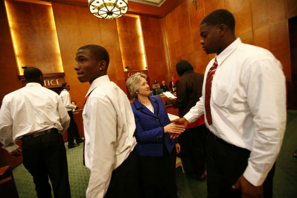 Houston City Mayor Annise Parker shakes hands with Chris Hill during a honoring of the Jack Yates High School basketball team at City Hall in Houston. The Yates Lions went 34-0 this season and won their second consecutive Class 4A state championship. They are ranked No. 1 in the country in all five national high school polls.