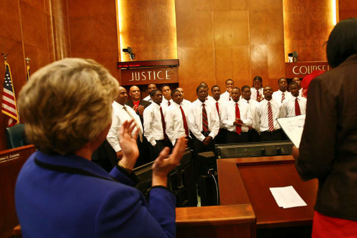 Houston City Mayor Annise Parker claps as Council Member Wanda Adams reads a proclamation in honor of the Jack Yates High School basketball team at City Hall.