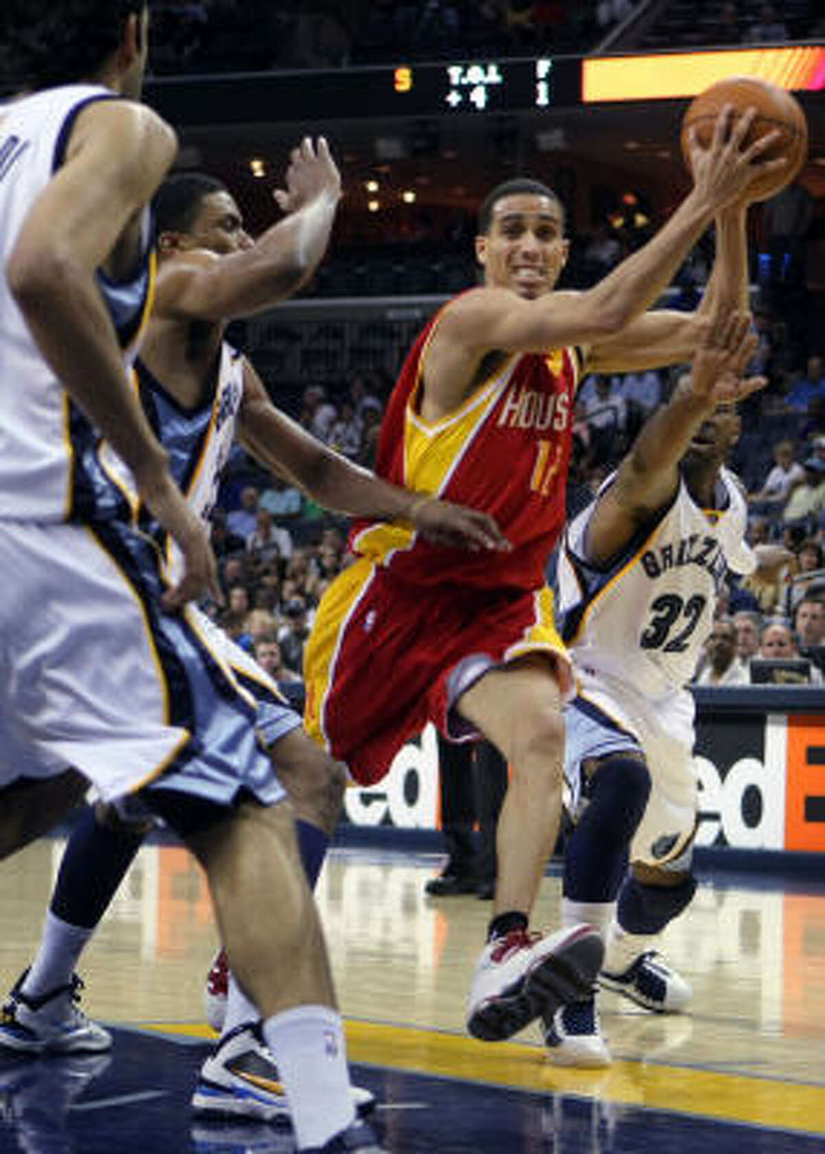 Rockets forward Kevin Martin drives to the basket under pressure from Grizzlies guard O.J. Mayo.
