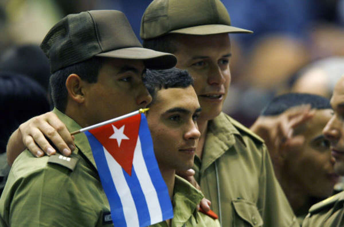 Elian Gonzalez, center, posses for a photograph along with two Cuban army soldiers during the Union of Young Communists, congress in Havana.