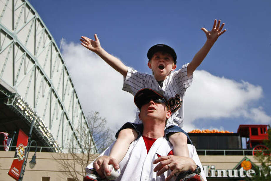 Tom Cabler holds his son Ty, 7, on his shoulders outside Minute Maid Park on Opening Day. Photo: Michael Paulsen, Chronicle