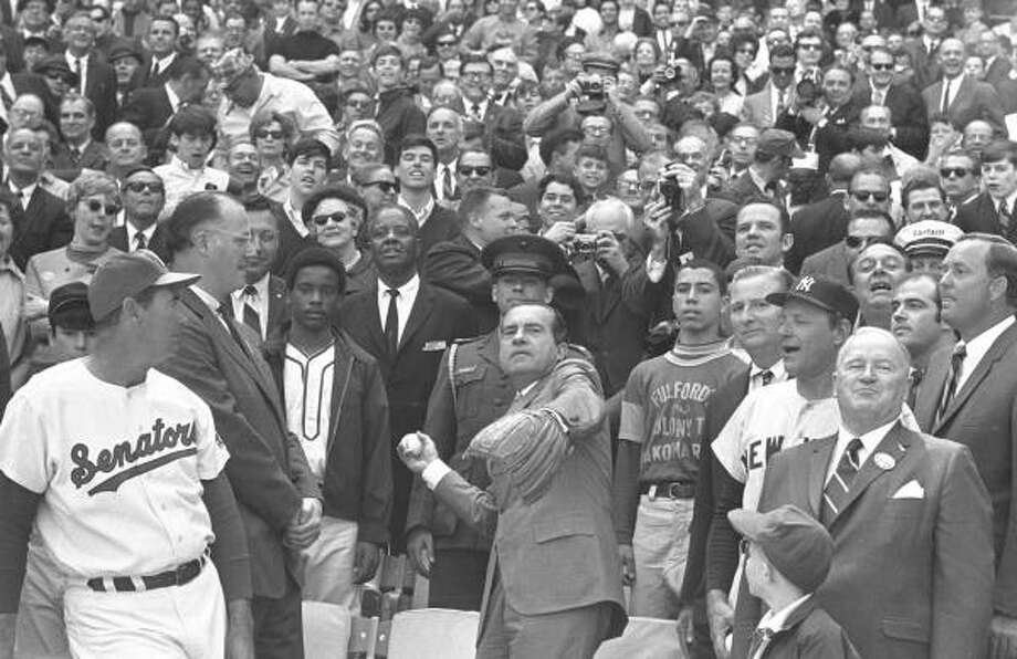 President Richard M. Nixon throws out the ceremonial first pitch in Washington as baseball commissioner Bowie Kuhn, second from left, and Washington Senators manager Ted Williams, and others, look on. Photo: AP