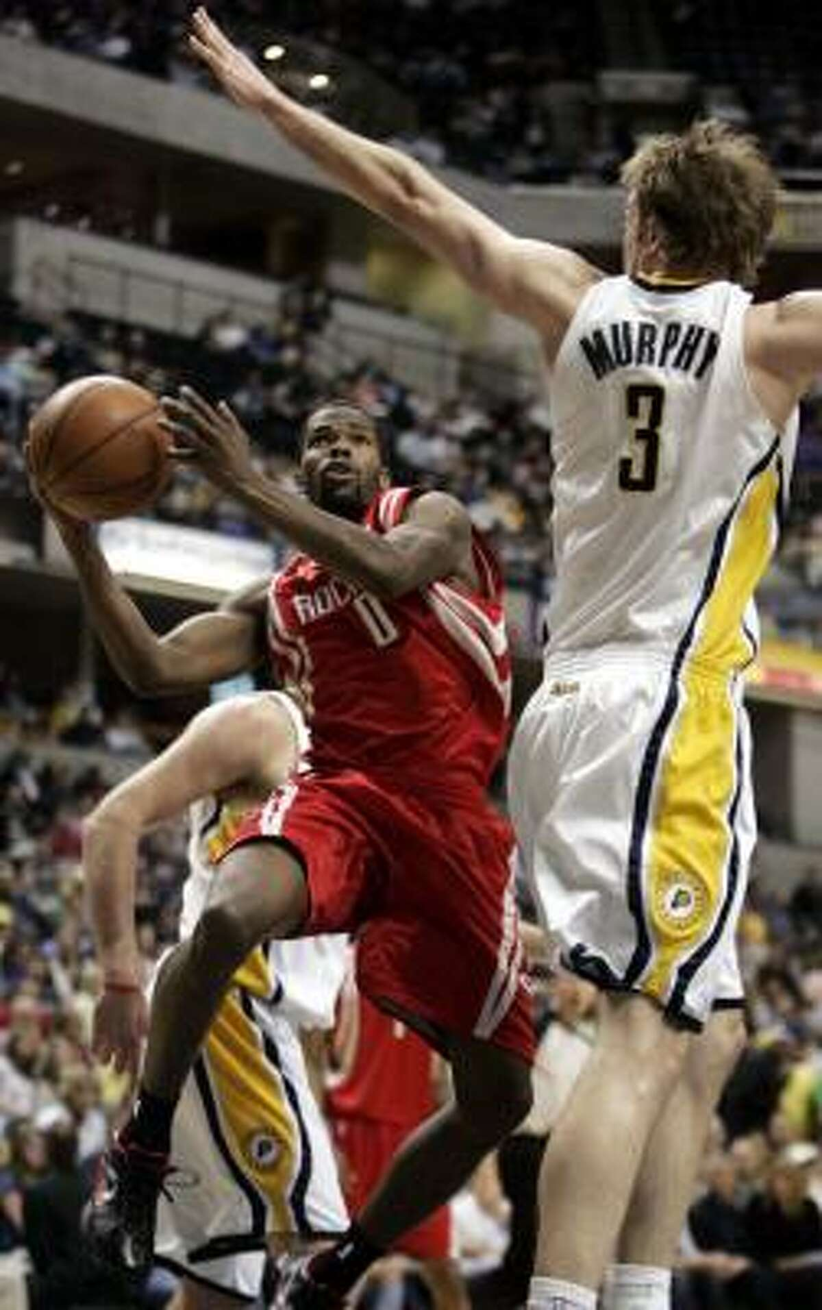 Rockets guard Aaron Brooks looks for room to shoot as he drives on Pacers' Troy Murphy.