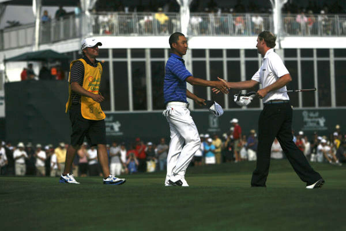 Anthony Kim, center, greets Vaughn Taylor after Kim won the final round of the Shell Houston Open.