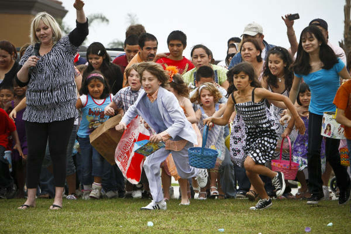 Matthew Woodfill, 11, (center) and other children rush to gather Easter Eggs at the Woodlands Christian Center where 5,000 eggs were dropped from a helicopter for the Easter Day celebration Sunday, April 4, 2010, in Spring.