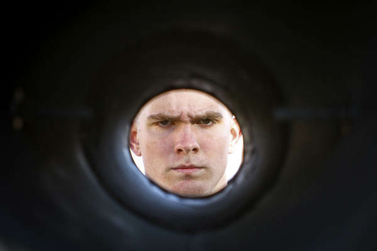Texas A&M cadet, Michael Froebel is framed inside a megaphone as he stands ready to play his trombone during the