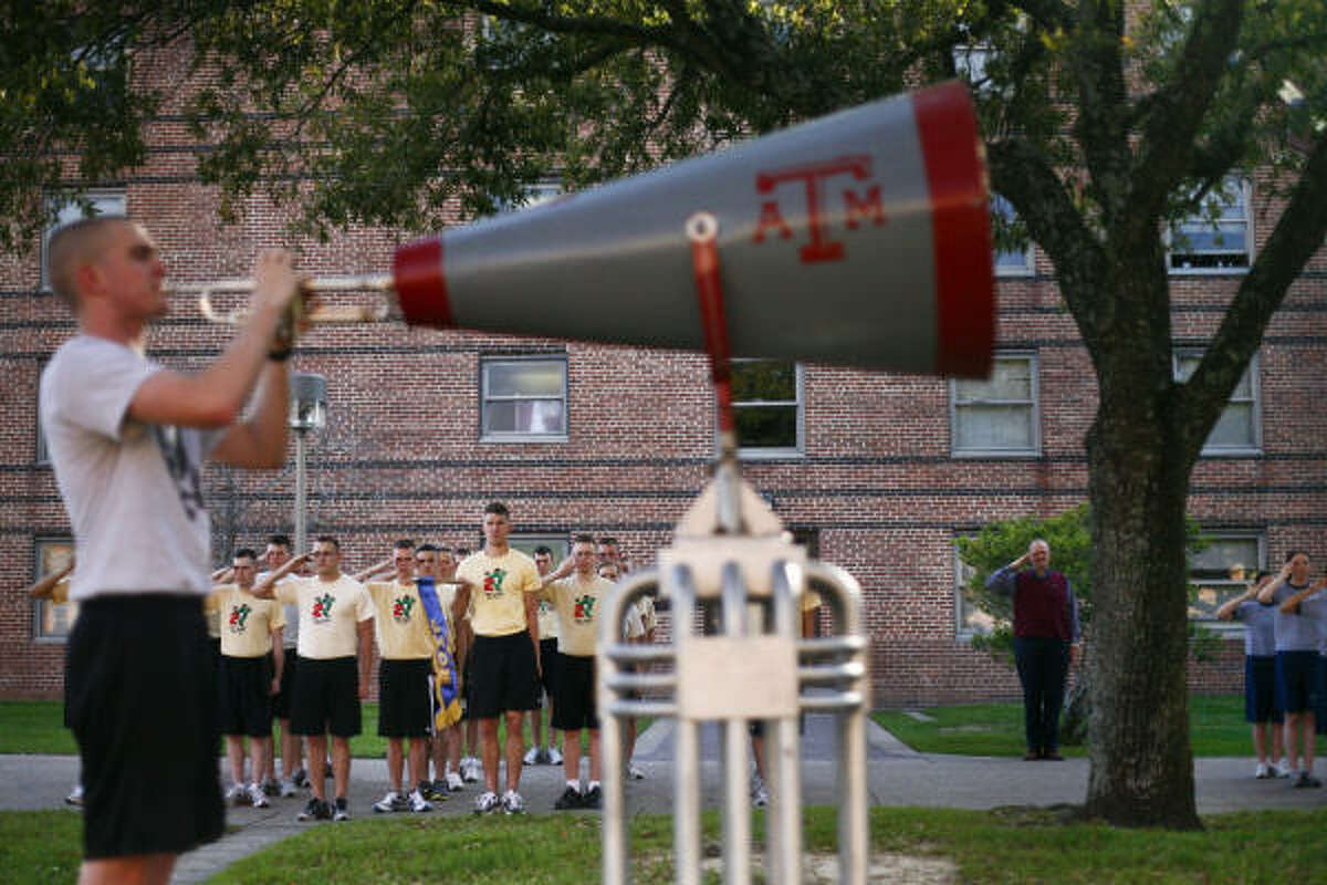 Texas A&M cadet, Michael Froebel plays his trumpet inside a megaphone during the
