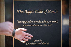 """A Texas A&M Corps cadet points to """"The Aggie Code of Honor"""" while giving a tour of the campus."""
