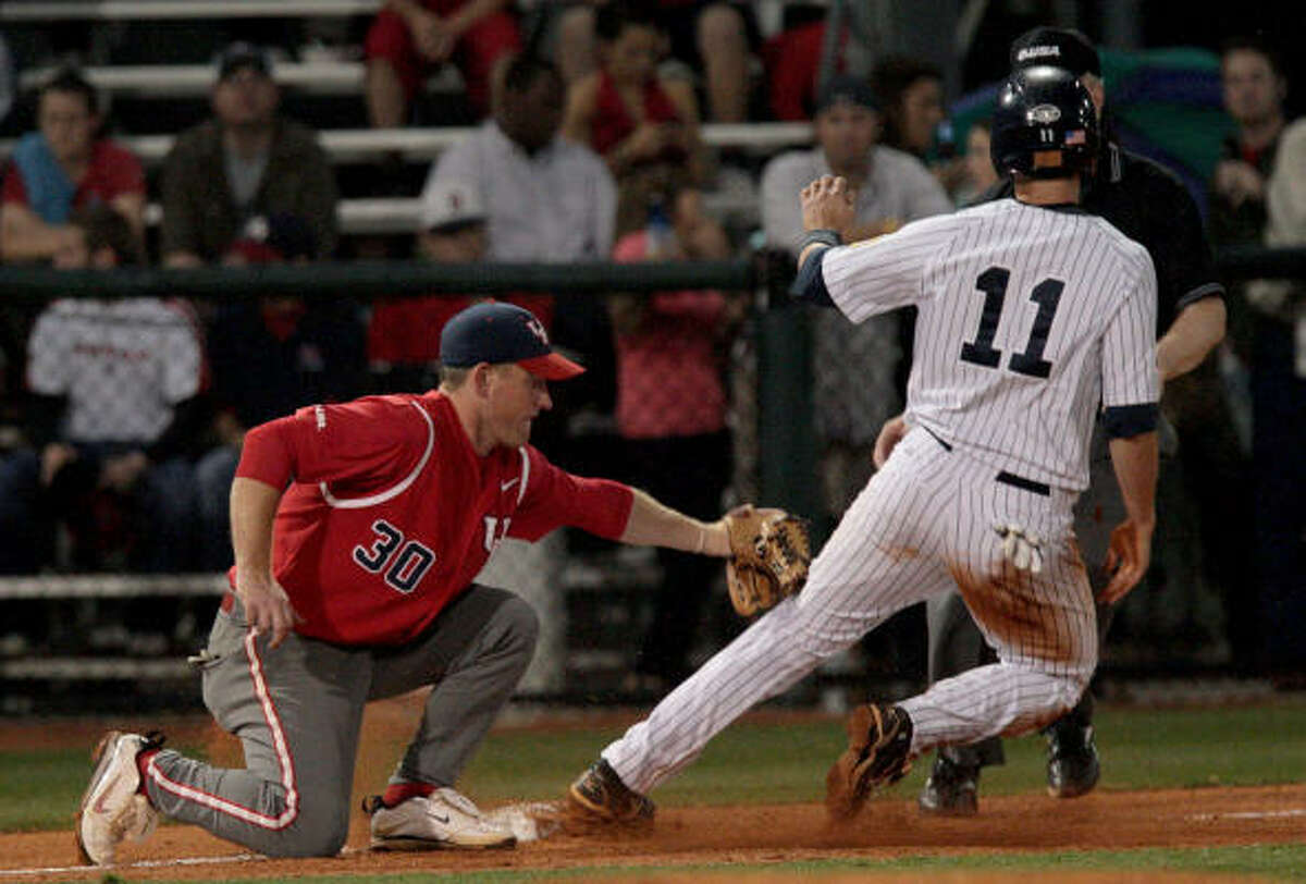UH third baseman Austin Gracey applies the tag late to Rice's Rick Hague, who stole third base in the fourth inning.